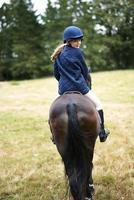 Rear view of girl horseback riding in field