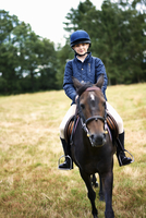 Portrait of girl horseback riding in field