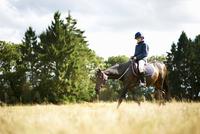 Girl horseback riding in field