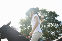 Cropped view of girl riding horse in countryside