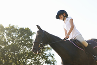 Low angle view of girl riding horse in countryside