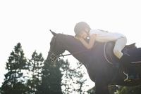 Girl on horseback leaning forward to pet horse