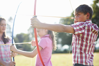 Girl practicing archery with teenage sister and brother