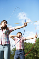 Teenage brother and sister practicing archery