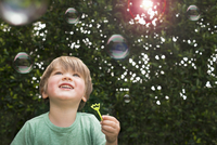 Young boy blowing bubbles, outdoors