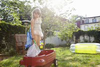 Girl in butterfly costume standing in toy wagon