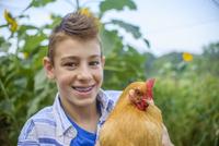 Portrait of boy in field holding hen