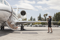 Female businesswoman preparing to board private jet at airport