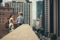 Businessman and woman talking on rooftop, Los Angeles, USA