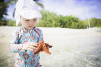 Girl on beach wearing swimwear and sunhat holding starfish looking down, St. Croix, US Virgin Islands