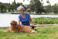 Mature woman sitting with dog in park