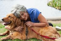 Mature woman hugging dog, outdoors