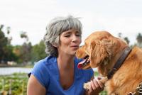 Mature woman petting dog, outdoors