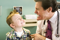 Male doctor looking at young boy's teeth