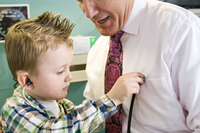 Male doctor letting young boy play with stethoscope in doctor's office