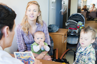 Mother sitting with two children, having discussion with doctor