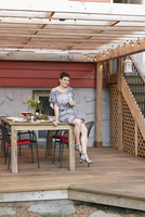 Portrait of mid adult woman sitting on patio table