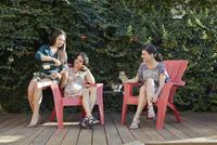 Three women drinking white wine on patio