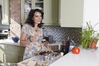 Mature woman preparing hummus in kitchen