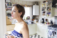 Mid adult woman drinking coffee and gazing from kitchen