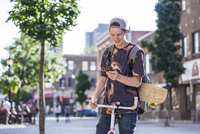 Young man using smartphone on bicycle, Le Plateau, Montreal, Quebec, Canada