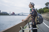 Young man with bicycle enjoying view by river, Le Plateau, Montreal, Quebec, Canada