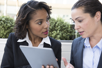 Two businesswomen looking at digital tablet, outdoors