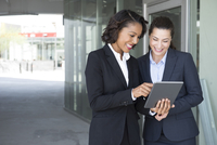 Two businesswomen, looking at digital tablet, outdoors