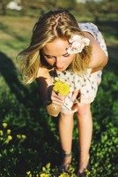 Young woman bending over smelling bunch of dandelion flowers