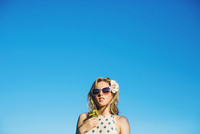 Low angle view of young woman wearing sunglasses, flowers in hair holding dandelion against blue sky
