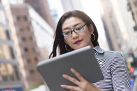 Businesswoman using digital tablet on street