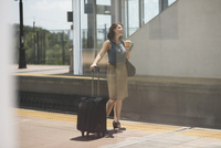 Mid adult woman waiting at train station, holding wheeled suitcase and coffee cup 11015263896| 写真素材・ストックフォト・画像・イラスト素材|アマナイメージズ