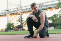Young man on sports track, kneeling, looking away