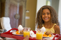 Young girl with breakfast tray looking at camera smiling