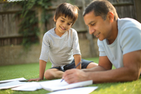 Boy sitting on grass watching father do paperwork looking down smiling