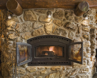 Lit fieldstone and rock fireplace in living room in cedar log home, Quebec, Canada