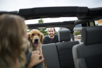 Young woman in jeep looking over her shoulder at dog and boyfriend