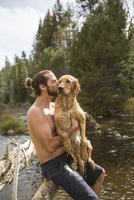 Young man kissing his wet dog at river, Lake Tahoe, Nevada, USA