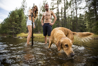 Young couple watching pet dog in river, Lake Tahoe, Nevada, USA