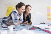 Mature women at desk resting on elbows using laptop smiling