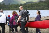 Group of people taking canoe out on lake, Cumbria, UK