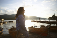 Mature woman sitting on canoe by lake, Lake District, Cumbria, UK