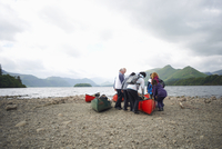 Group of people standing by canoe at lake edge, Lake District, Cumbria, UK