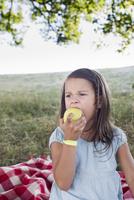 Girl eating green apple at park picnic