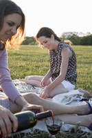 Two mature female friends pouring red wine in park