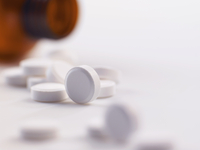 Pain killer pills spilling out of a bottle
