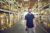 Portrait of male warehouse worker standing in distribution warehouse aisle 11015264851| 写真素材・ストックフォト・画像・イラスト素材|アマナイメージズ