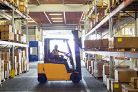 Silhouetted forklift truck at work in distribution warehouse