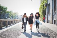Three stylish young female friends strolling along sidewalk