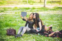 Young female friends sitting in park taking digital tablet selfie